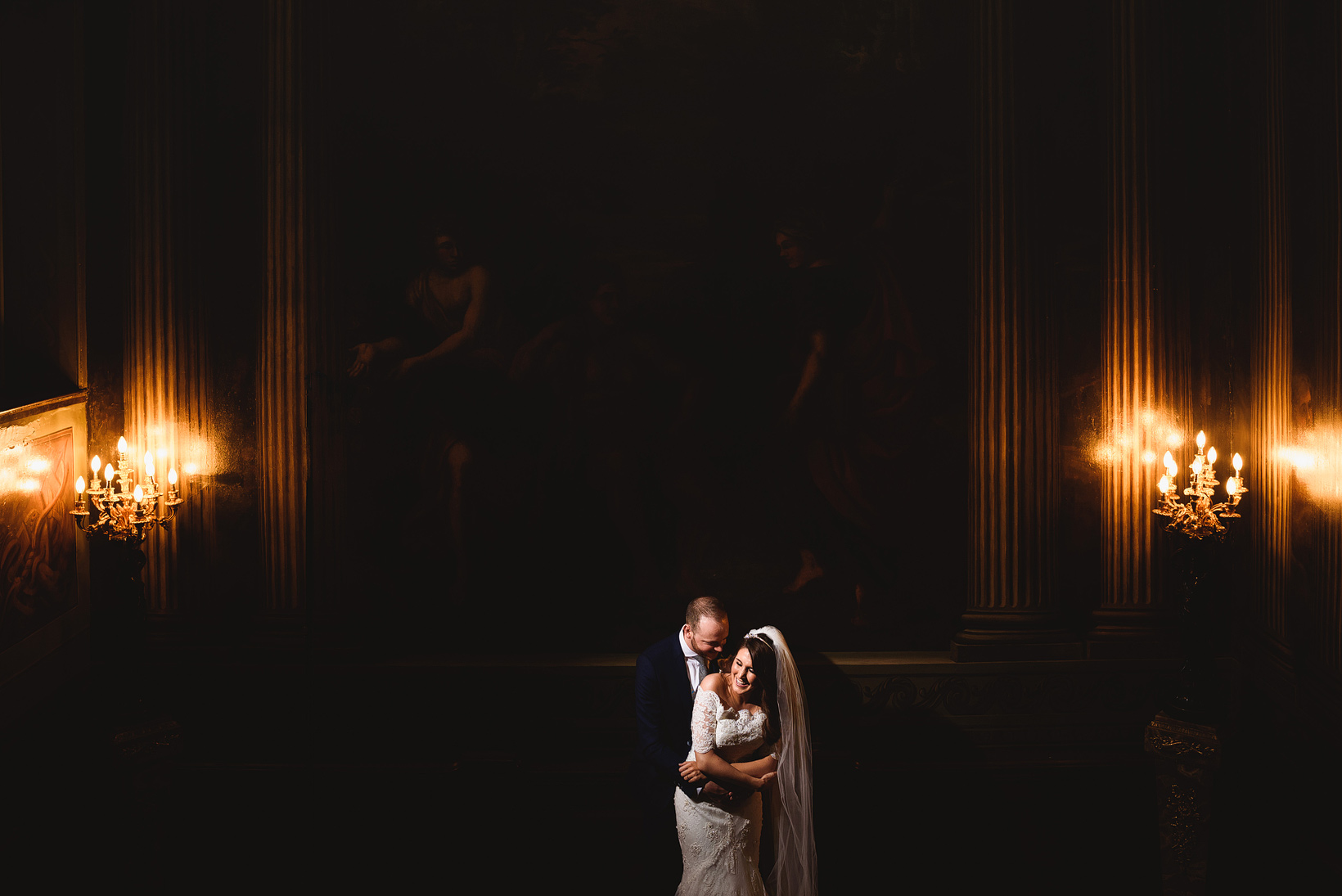 bride and groom pose in front of grand painting